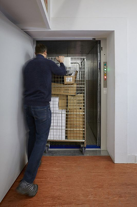 a Stannah trolley lift transporting large quantities of goods between floors in a retail store