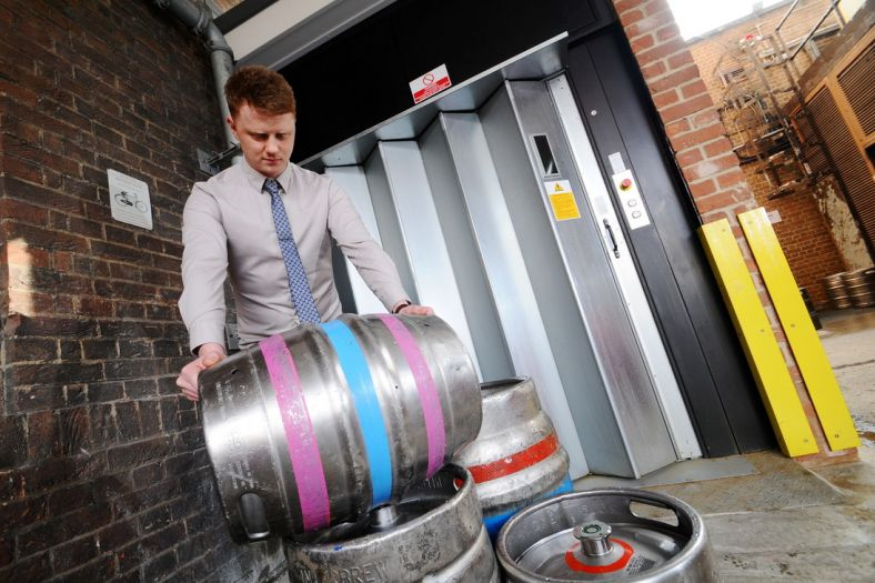 A goods lift moving beer barrels to a mezzanine floor in a national pub chain