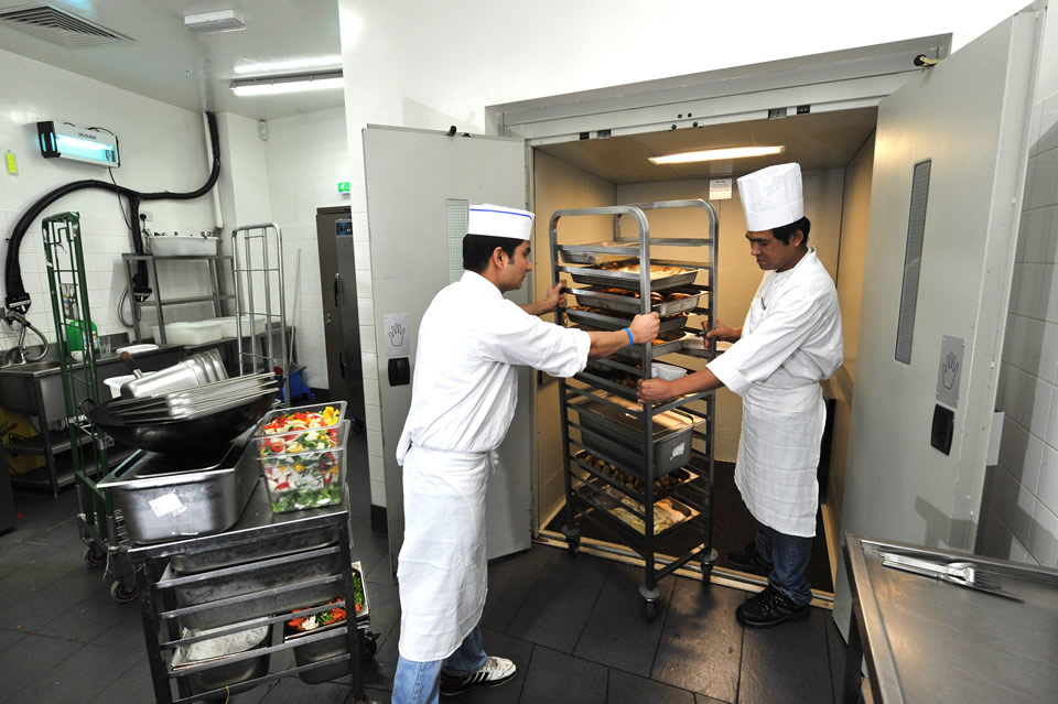 two chefs loading a trolley of food into a goods lift